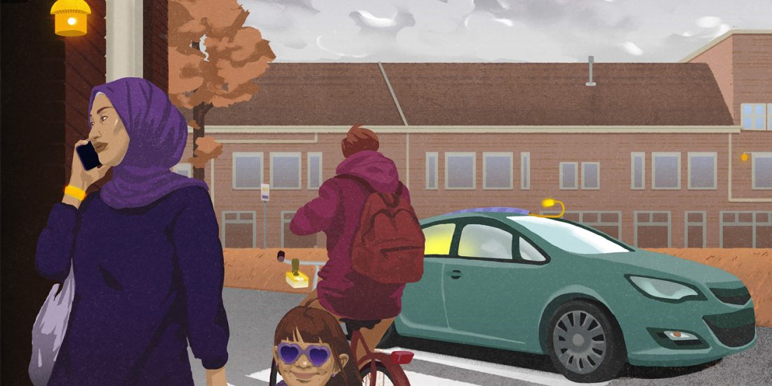 A woman with an hijab talks on the phone and hold a little girl's hand while they cross the street. A man on a bike is behind them, and a car comes the opposite way. There are sensors above them and around them.